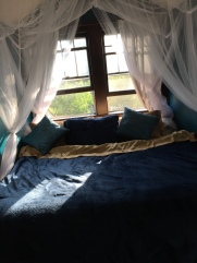 My nest, surrounded by seafoam blues, gauzy curtains, and twinkle lights.
