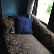 Reading nook on a gold and navy chaise.